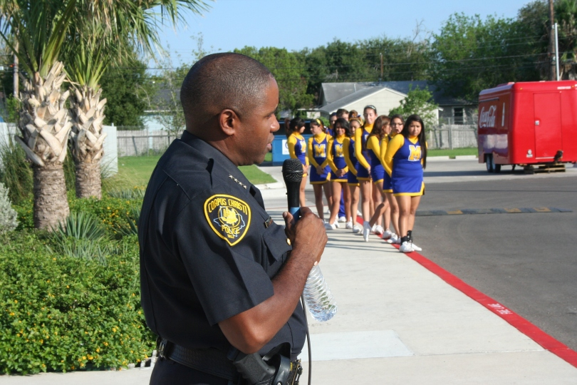 Corpus Christi Police Chief Floyd Simpson addresses the crowd for the National Night Out kick-off event at the HEB on Kostoryz as the Moody Trojan Cheerleaders are ready to perform