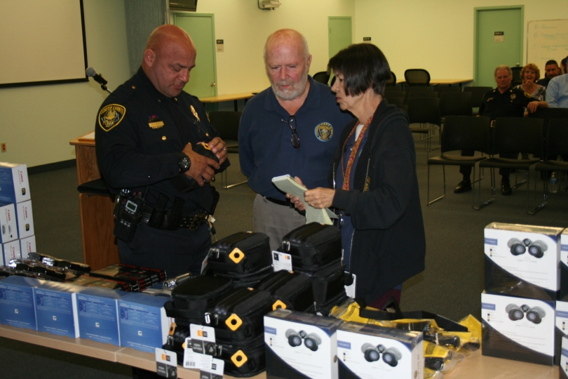Assitant Chief Mike Markle looks at donated equipment as Citizens Police Academy Alumni Vice President Bob Mitchell and incomming President Cheryl Daubs explain the display