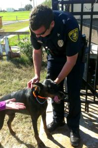 Senior Officer Jason Lee stands with the dog moments after the rescue