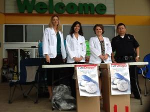 Pharmacy students Lisa Eggleston, Angelic Toy, and Heather Goodman wait to accept the medications with Officer Cervantes at the HEB in Flour Bluff.