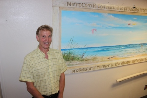 Local artist Patrick Richard with his artwork which he donated to honor Metrocom